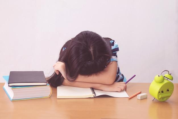 Gelangweilte und müde asiatische studentin, die hausaufgaben macht
