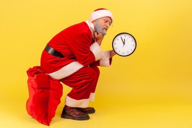 Gelangweilter älterer mann mit weihnachtsmann-kostüm, der auf einer großen roten tasche mit geschenken sitzt und die wanduhr in den händen hält, wartezeit, um ein geschenk zu geben. innenstudio erschossen auf gelbem hintergrund.