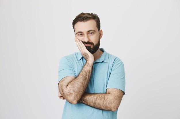 Gelangweilter erwachsener mann sieht uninteressiert aus, mageres gesicht auf handfläche