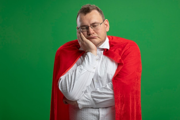 Gelangweilter erwachsener superheldenmann im roten umhang, der die brille trägt, die hand auf gesicht setzt, das gerade lokal auf grüner wand schaut