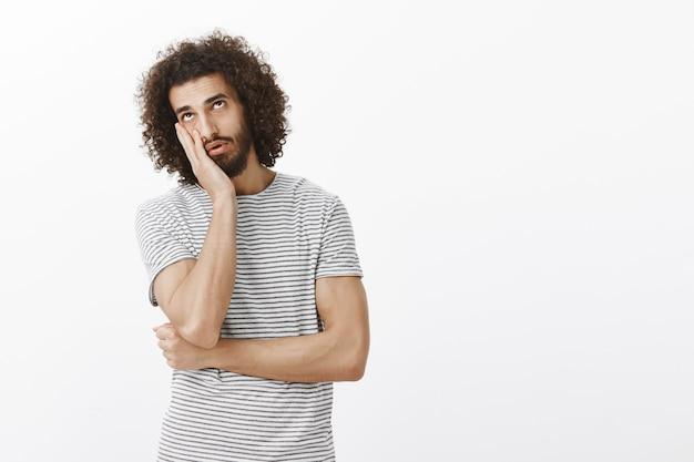 Gelangweilter gleichgültiger gutaussehender spanischer mann mit bart und afro-frisur, der gesichtspalme macht und mit müde und sattem ausdruck aufblickt