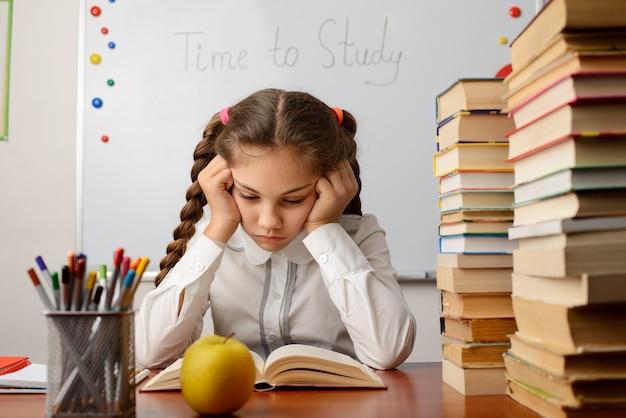 Gelangweilter grundschüler, der ein buch liest
