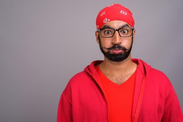 Gelangweilter indischer mann, der rotes hemd trägt und lustiges gesicht macht
