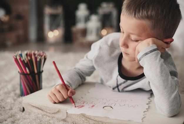 Gelangweilter junge, der auf boden zeichnet