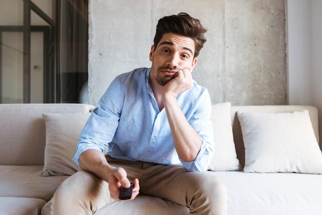 Gelangweilter junger mann, der fernsehfernbedienung hält