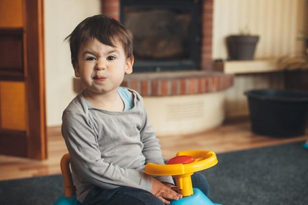 Gelangweilter kaukasischer junge, der im wohnzimmer beim fahren eines plastikautos aufwirft und vorne schaut