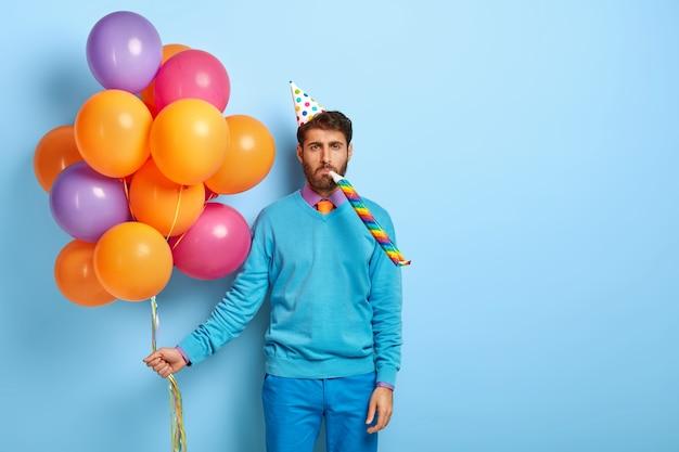Gelangweilter kerl mit geburtstagshut und luftballons, die im blauen pullover aufwerfen