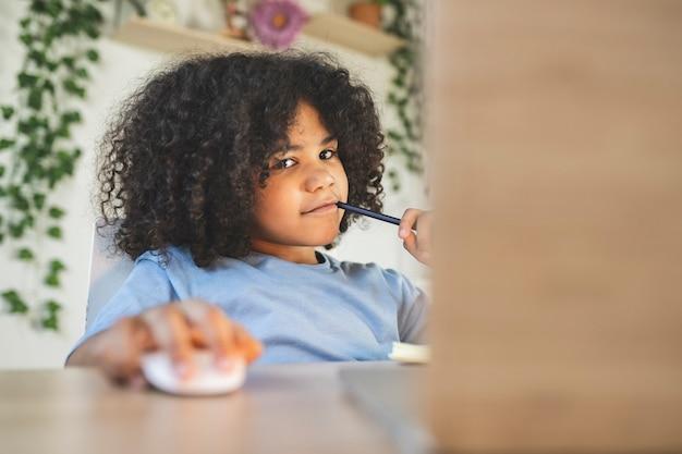 Gelangweilter kleiner junge beim hausaufgaben machen am computer