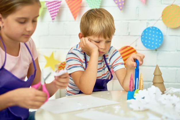 Gelangweilter kleiner junge in der handwerksklasse