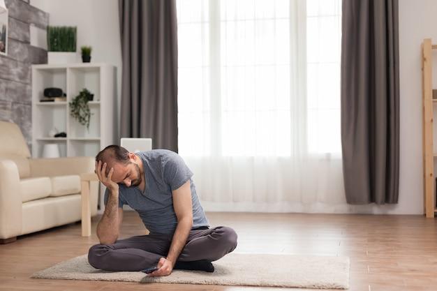 Gelangweilter mann, der während der quarantäne auf einem teppich im wohnzimmer sitzt und auf dem smartphone surft.