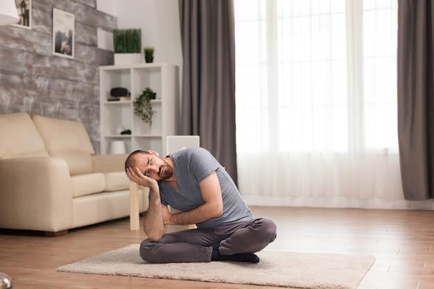 Gelangweilter mann, der während der selbstisolation auf teppich im wohnzimmer sitzt.