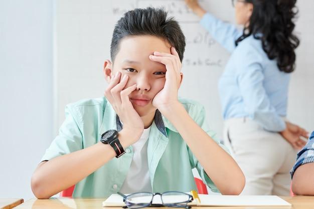 Gelangweilter müder vietnamesischer shoolboy, der am schreibtisch im matheunterricht sitzt