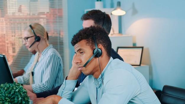 Gelangweilter multiethnischer kundenbetreuer, der auf einen telefonanruf des kunden wartet