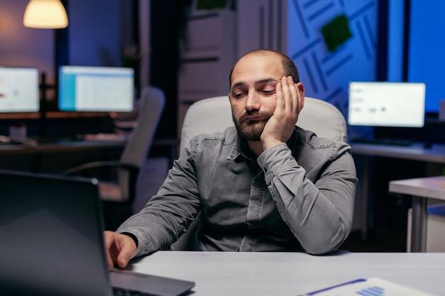 Gelangweilter schläfriger geschäftsmann, der am laptop arbeitet und überstunden am arbeitsplatz macht. workaholic-mitarbeiter schläft ein, weil er spät nachts allein im büro für ein wichtiges unternehmensprojekt arbeitet.