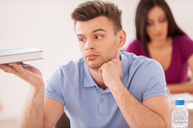 Gelangweilter student. hübscher männlicher student, der die hand am kinn hält und das lehrbuch betrachtet, während die junge frau hinter ihm am schreibtisch sitzt