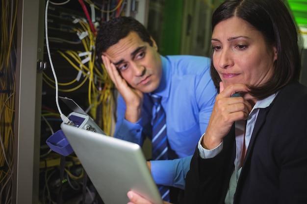 Gelangweilter techniker, der kollegen beim analysieren des servers betrachtet