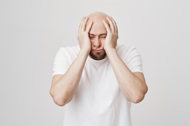 Gelangweilter und düsterer glatzkopf greift deprimiert nach dem kopf
