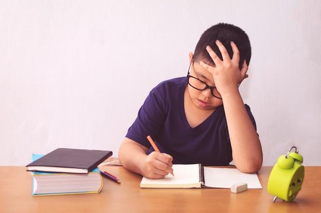 Gelangweilter und müder asiatischer studentenjunge, der hausaufgaben macht