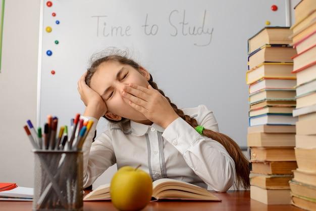 Gelangweilter und müder grundschüler gähnt wegen ständigem lernen
