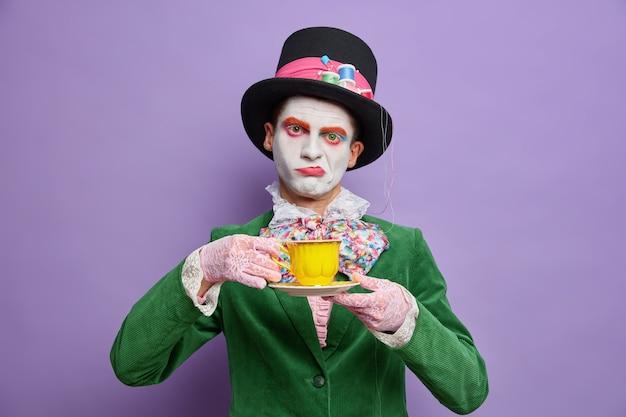 Gelangweilter unzufriedener mann hutmacher besessen von tee trinken trägt großen hut grünes kostüm fliege posiert gegen lila wand kommt auf gruselige party feiert halloween steht drinnen