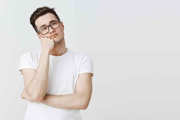 Gelangweilter widerstrebender kerl in brille, auf die hand gelehnt und ohne interesse schauend