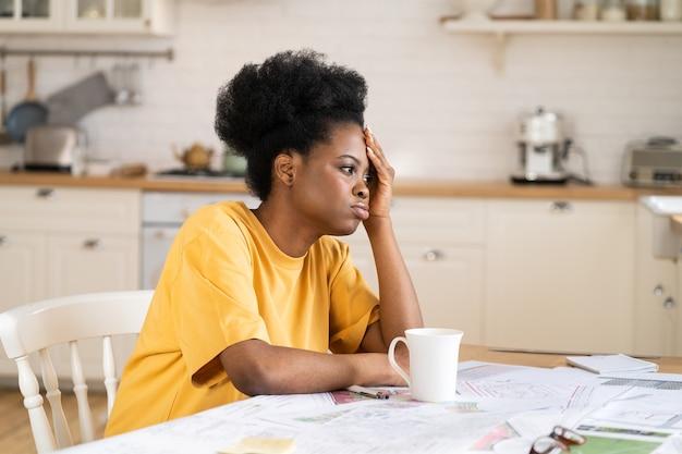 Gelangweiltes afrikanisches mädchen, das es satt hat, freiberuflich zu arbeiten, sitzt frustriert am schreibtisch zu hause mit papieren