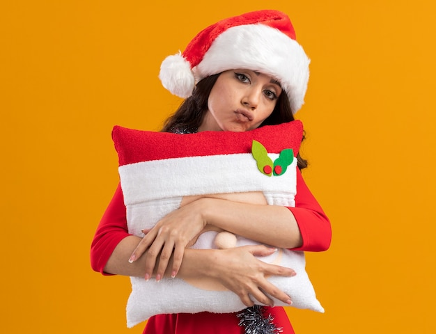 Gelangweiltes junges hübsches mädchen mit weihnachtsmütze und lametta-girlande um den hals, das das weihnachtsmann-kissen umarmt, das die lippen isoliert auf der orangefarbenen wand schürzt