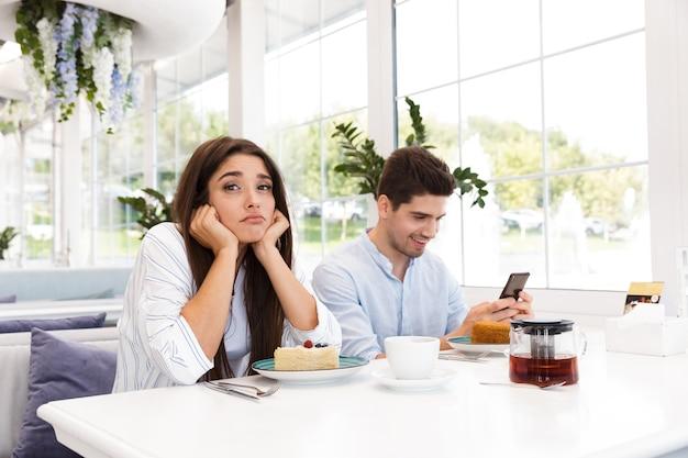 Gelangweiltes junges mädchen, das am kaffeetisch sitzt, während ihr freund handy benutzt