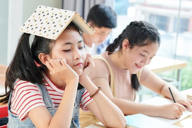 Gelangweiltes junges mädchen, das an der schulbank mit geöffnetem buch auf ihrem kopf sitzt, während ihr lächelnder klassenkamerad im heft schreibt