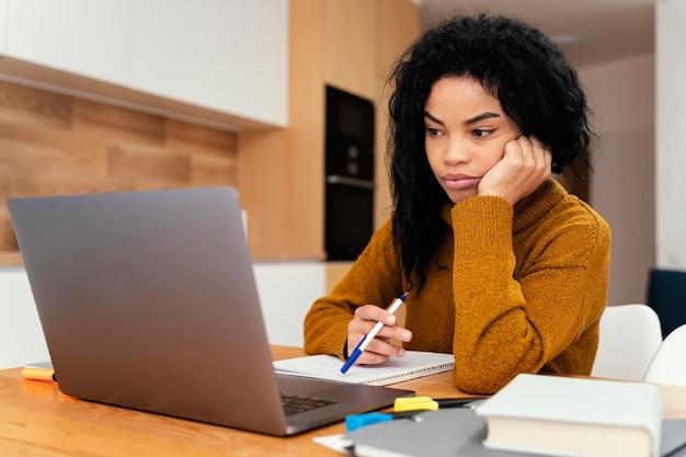 Gelangweiltes junges mädchen zu hause während der online-schule