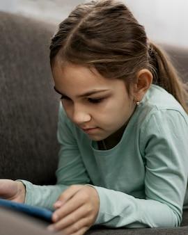 Gelangweiltes kleines mädchen, das zu hause auf einem smartphone spielt