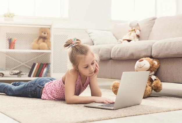 Gelangweiltes kleines mädchen mit laptop zu hause. nettes kind, das hausaufgaben am computer macht. modernes online-bildungs-, kommunikations- und technologiekonzept, kopierraum