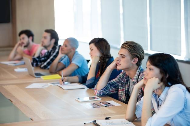 Gelangweiltes kreatives geschäftsteam, das an einer besprechung im konferenzraum teilnimmt