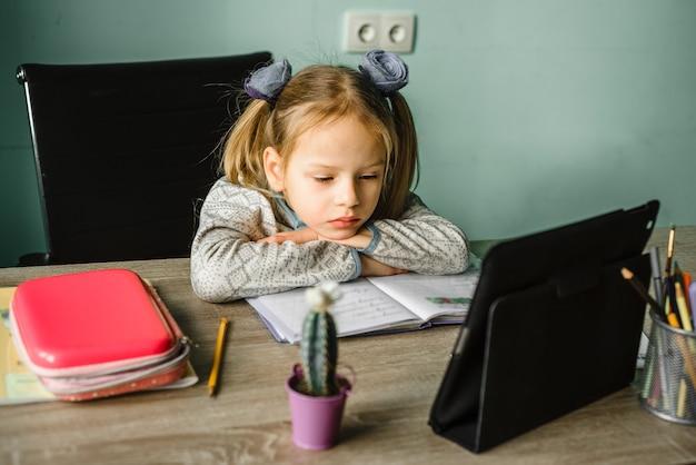 Gelangweiltes schulmädchen, das sich auf ihre arme stützt, während es zu hause online-unterricht hat