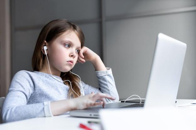 Gelangweiltes teenager-mädchen, das des online-computerunterrichts müde ist, schaut zu hause traurig auf den monitor