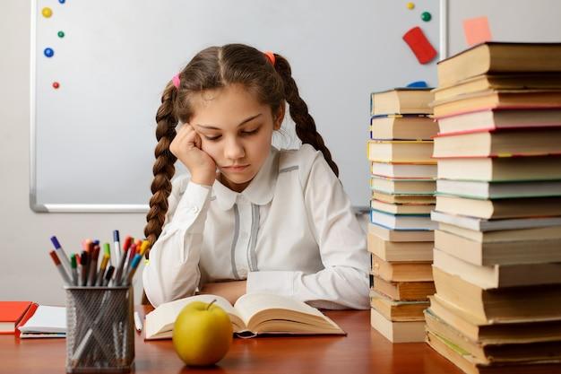 Gelangweiltes und müdes mädchen, das ein buch im klassenzimmer liest