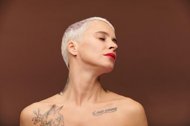 Gelassene frau mit kurzen blonden haaren, geschlossenen augen, tätowierungen an hals und brust und rotem lippenstift auf den lippen, die ihren kopf isoliert zur seite gedreht hält