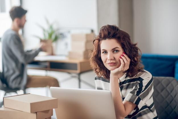 Gelassener büroangestellter sitzt am laptop