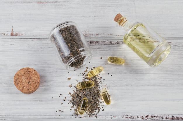 Gelatinekapseln mit algen-omega-öl und seetang auf weißem holz. nahrungsergänzungsmittel.