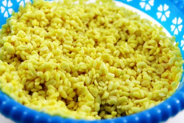 Gelb aufgeteilter mungodal oder moong dal stapel lokalisiert auf weißem hintergrund