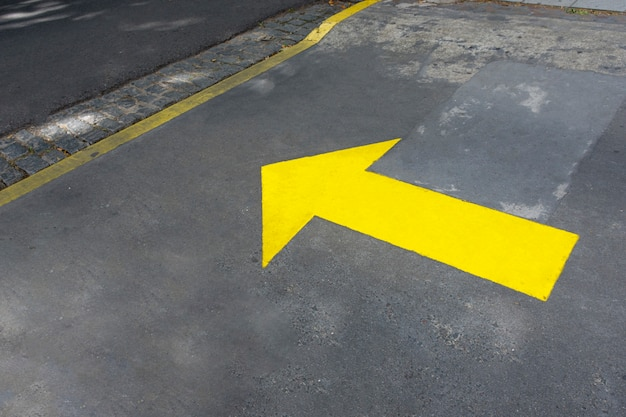 Gelb gemalter pfeil in den straßen