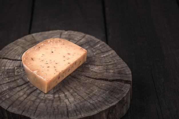 Gelb geräucherter würziger käse auf einem holzende eines baumes
