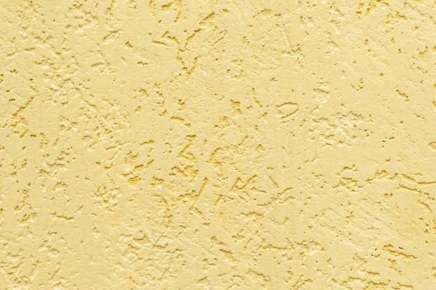 Gelb gestrichene geprägte wand, textur aus zierputz mit relief, fragment der gebäudefassadendekoration im borkenkäferstil