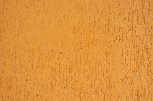 Gelb gestrichene wand mit strukturiertem bild mit pinselstrich, ansicht von oben. wand gelb gestrichen. gelber beton