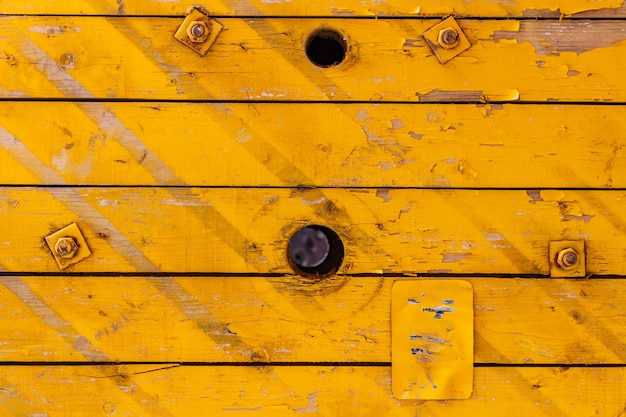 Gelb lackierte alte holzbretter mit löchern. natürliche holzstruktur. abstrakter hintergrund