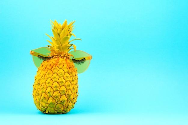 Gelb lackierte ananas in sonnenbrille mit künstlichen wimpern