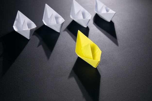 Gelb mit weißem papierboot auf schwarzer oberfläche
