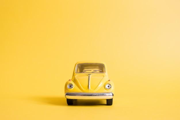 Gelb. retro spielzeugauto auf gelb. sommer reisekonzept. taxi