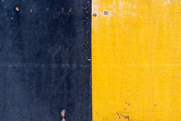 Gelb-schwarzer stahl weist abrieb durch gebrauch und dauer auf.