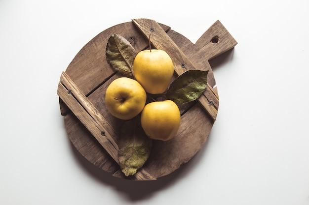 Gelbe äpfel auf einem geschnittenen brett im vintage-stil. blätter, lebensmittel, gesunde lebensmittel, vegan, landwirtschaftliche produkte.